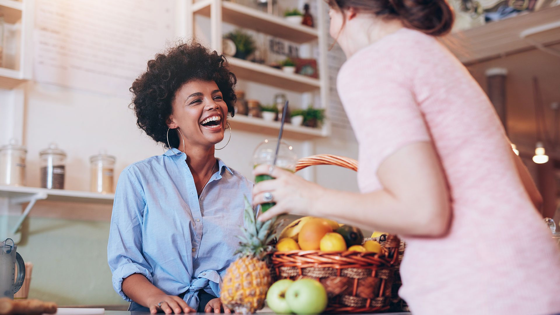 Female store owner smiling with client at checkout counter